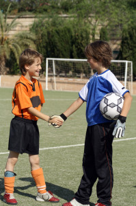 kids shaking hands before football or soccer match